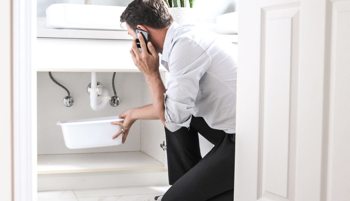 Man Calling Plumber In Front Of Water Leaking From Sink Pipe