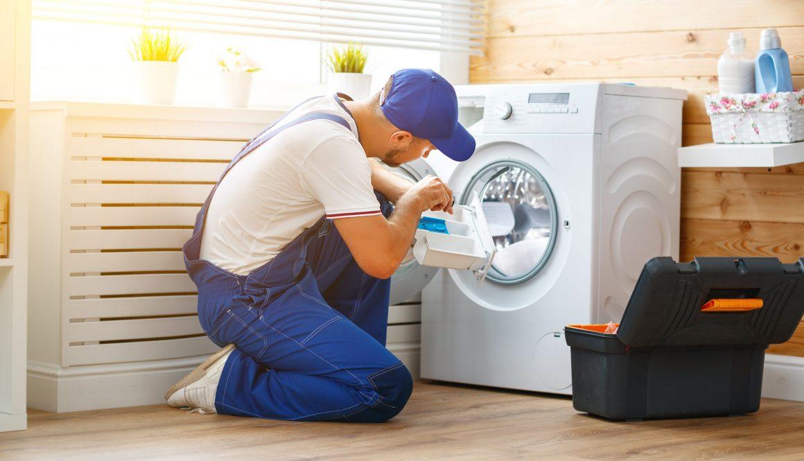 working man   plumber repairs  washing machine in   laundry